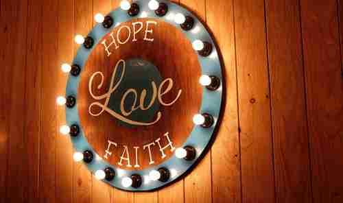 servant leader: round wall light with words faith love hope.