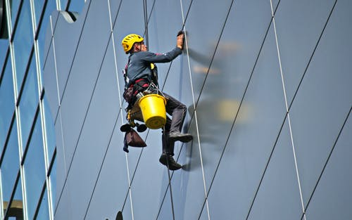 man suspended cleaning windows: exterior cleaning services