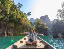 top new travel apps: woman on a canoe on a blue lake