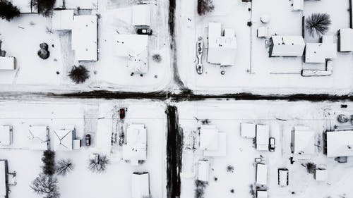 how to protect your roof: overhead photo of snow covered roofs.