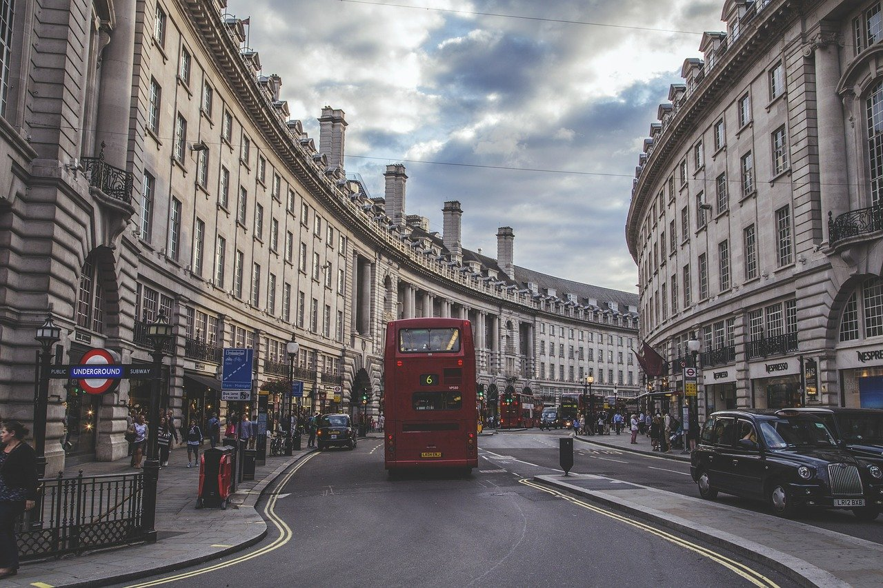 London on a budget: red double decker bus going down Regent Street.