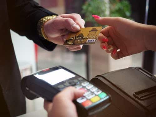 worried about money: man paying in ship using chip and pin machine