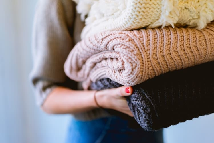 woman holding knitted jumpers
