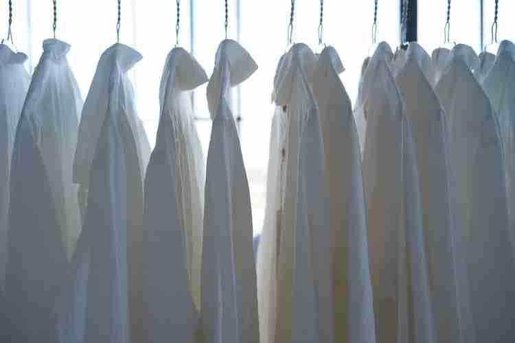girl boss capsule wardrobe: white shirts hanging on rail