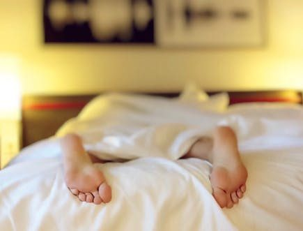person lying on stomach with feet dangling off bed: buying adjustable bed sets.