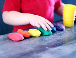 finding the best child care: small child playing with different colours of playdough.