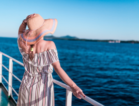 woman looking to land from side of ship: first day on a cruise