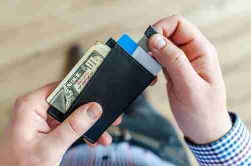 side hustle ideas: man opening black wallet.