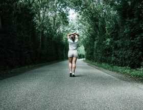 running safety tips: rear shot of woman running on narrow country road