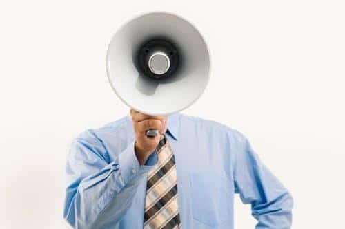 soundproofing expert advice: man in shirt and tie with a loudspeaker.