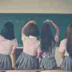 the right corporate uniform: 4 school girls facing balckboard in school uniform