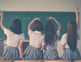 the right corporate uniform: 4 school girls facing balckboard in school uniform