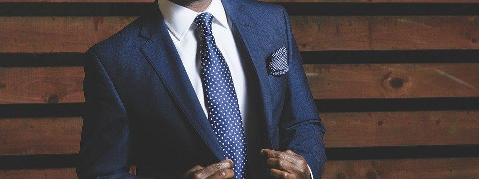 buying custom tailored suits: man wearing blue suit, white shirt and blue tie