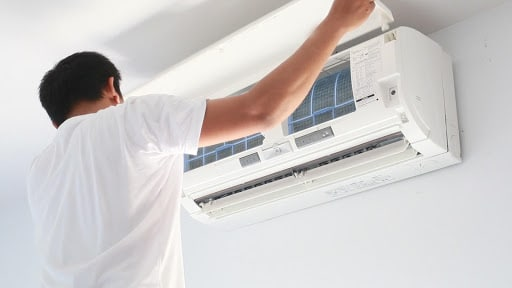 Technician fitting an AC unit