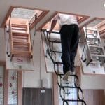 man going up attic starirs