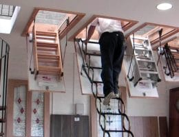 man going up attic starirs
