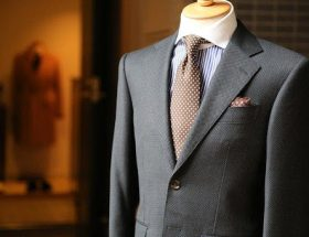 buying custom tailored suits: grey suit with brown tie on mannequin