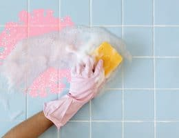 person cleaning bathroom tiles by hand: best cleaner devices for tiles.