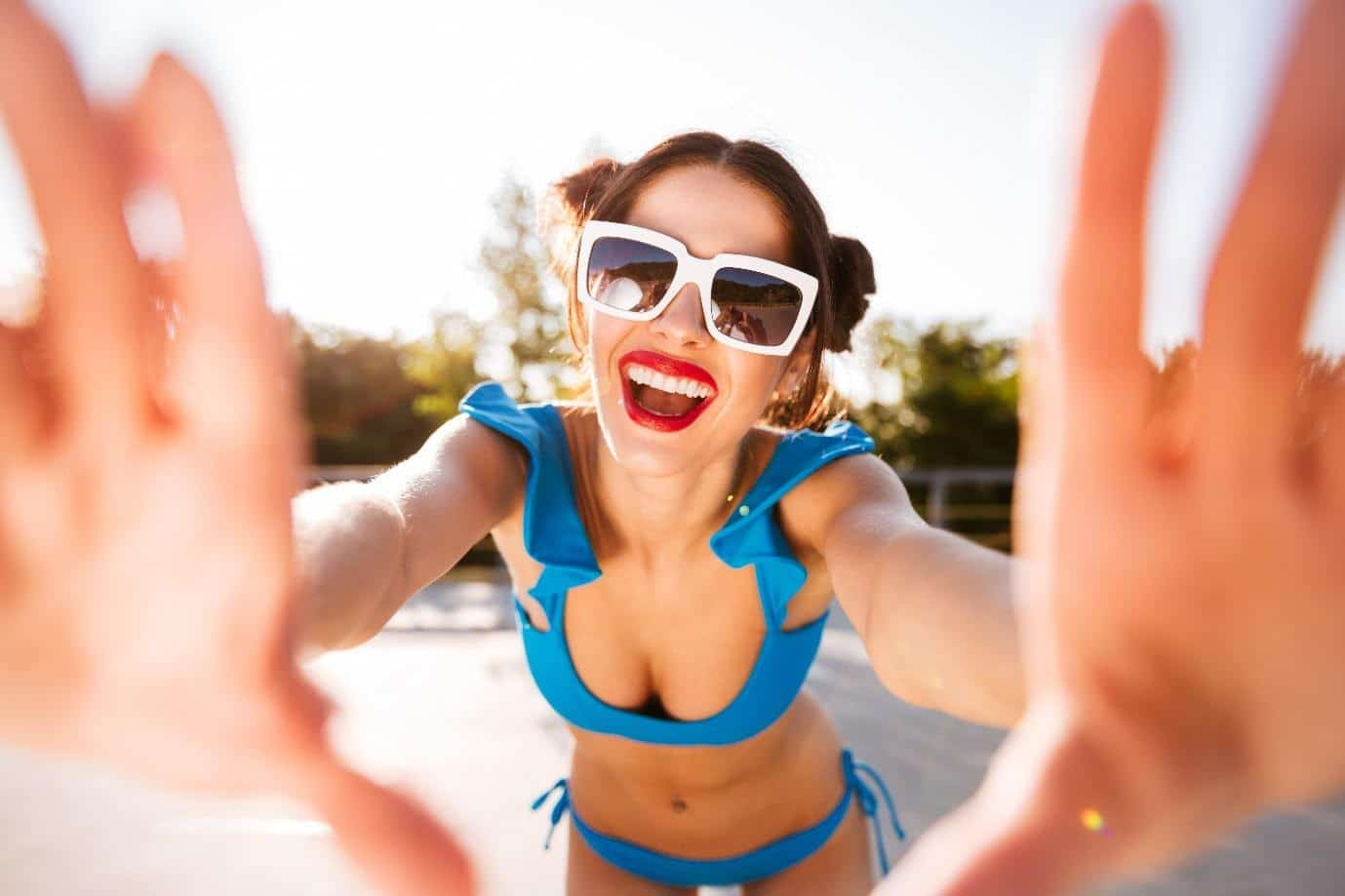 how to know your sunglasses have UV protection: young woman laughing wearing sunglasses