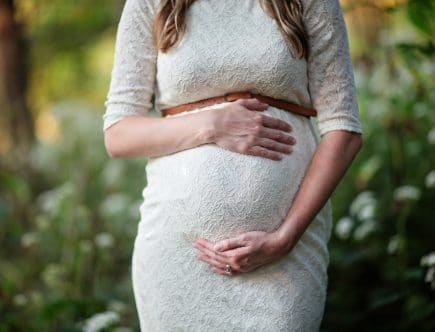 guide to maternity clothing - pregnant woman in white dress holding her tummy.