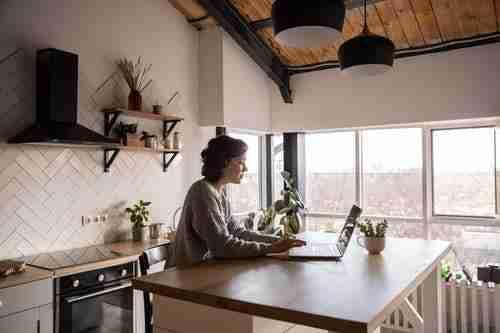 woman on laptop in kitchen: earn money online