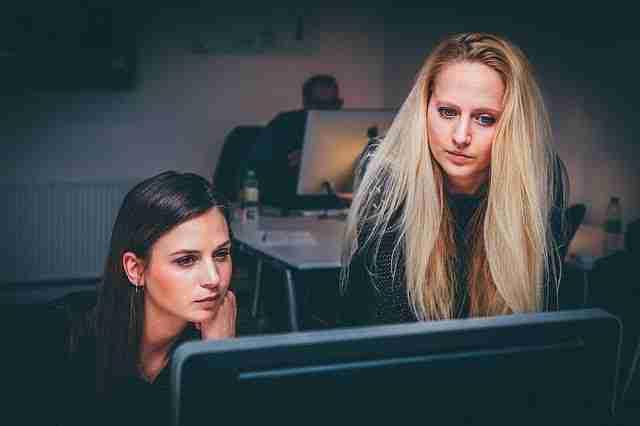 2 women looking at a computer screen: run a better business.
