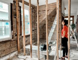 prioritize home maintenance@ young woman standing in room with small scaffold.