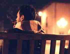 life insurance for smokers: man smoking on park bench at night.
