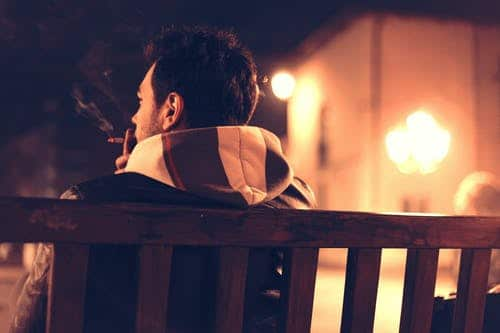 life insurance for smokers: man smoking on park bench at night.