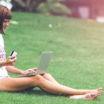 benefits of shopping online: woman sitting on grass in park with laptop and holding bank card