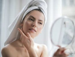 best eco friendly towels: young woman with towel on her head looking at herself in the mirror.