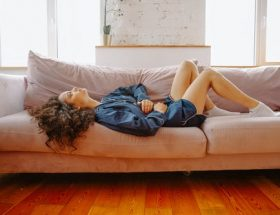 get tested for coeliac disease: woman lying on sofa in gown, holding her stomach.