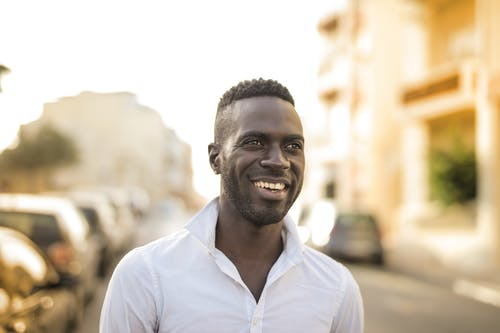 stress free happy life: black man wearing white shirt smiling.