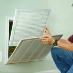are your air filters working? Man checking air filters in wall.