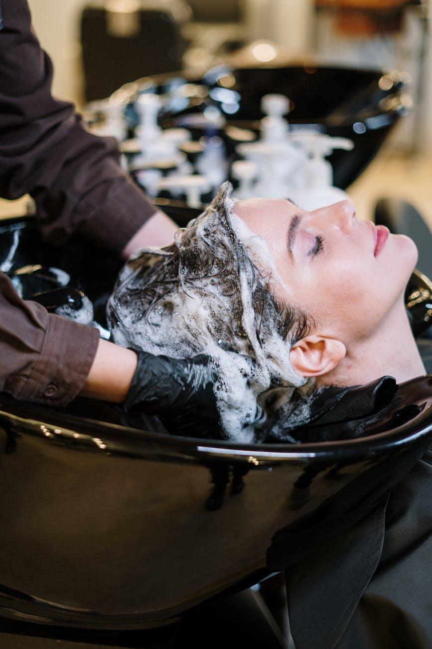 woman getting her hair washed at a hair salon: hair loss myths