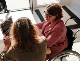 qualify for social security disability: woman in a wheelchair sitting at laptop at desk with another woman beside her.