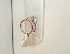 key with a heart keychain in a door