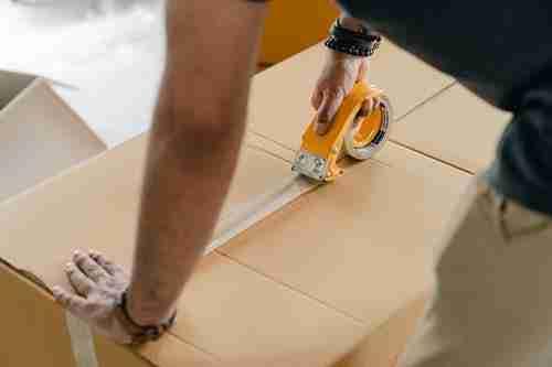 storage unit organization: man boxing up items.
