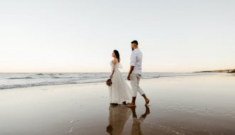before planning a wedding: couple walking on a beach after wedding