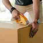 safe storage Sydney: man boxingup a box with tape.