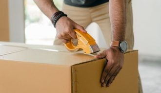 safe storage Sydney: man boxingup a box with tape.