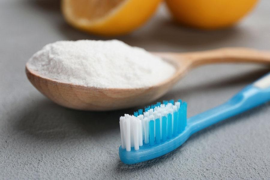 Baking soda in a wooden spoon and blue toothbrush beside it.