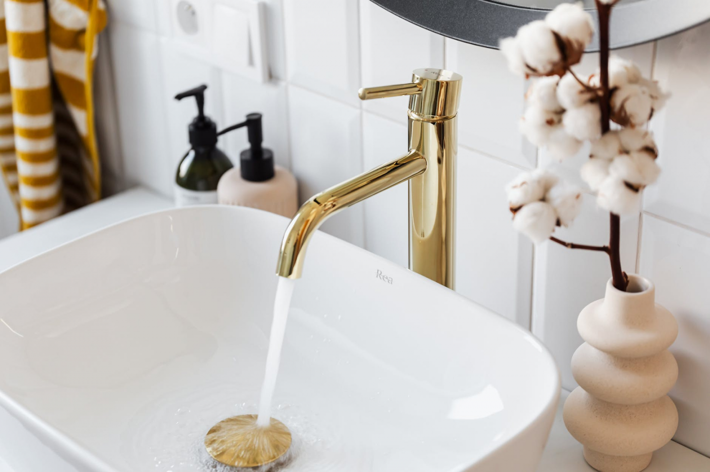 ideas for small bathrooms. Gold plated tap running water in white sink basin.