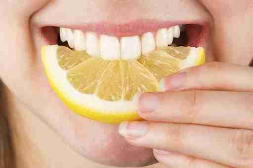 Lemon for teeth whitening. Woman biting a lemon sllice.
