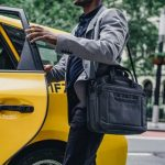male high end fashion. Man getting into a yellow taxi.