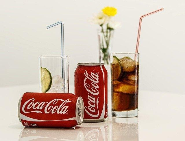 2 cans of coca cola and a glass of coca cola.