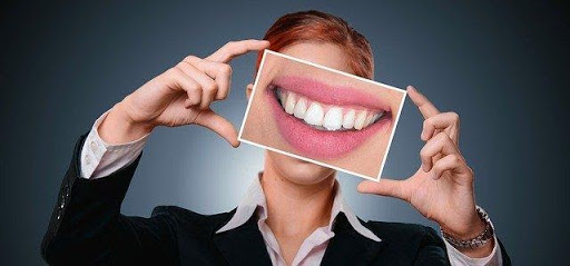 causes of yellow teeth: man holding picture of white teeth.