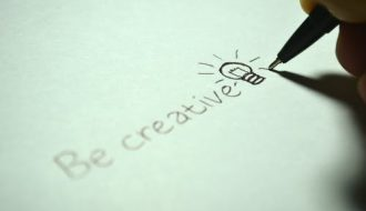 "person writing ""Be creative"" and a picture of a lightbulb on paper with a sharp pencil. Your creative flair."