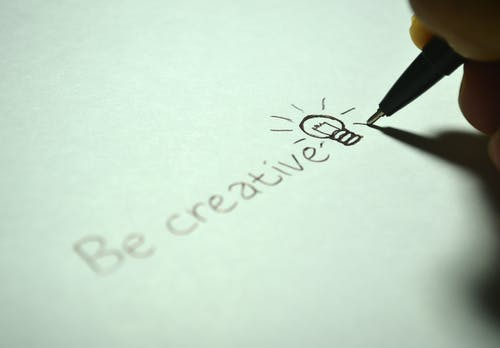 """person writing """"Be creative"""" and a picture of a lightbulb on paper with a sharp pencil. Your creative flair."""