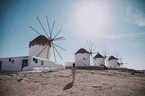 Woman walking towards set of windmills on a hill. Reasons to visit Mykonos.